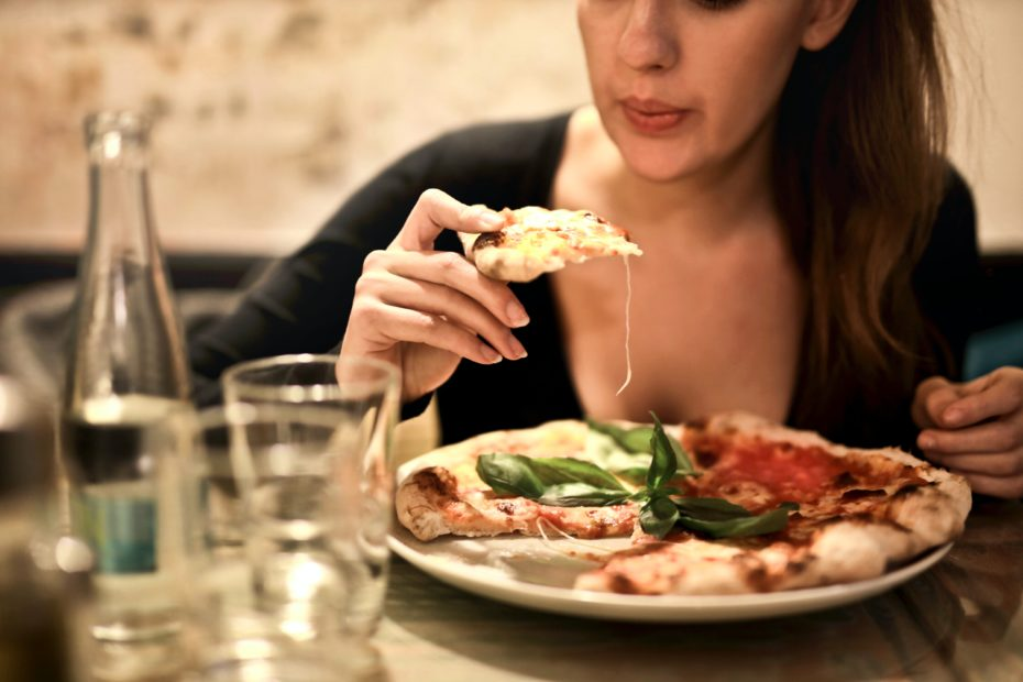 woman-holds-sliced-pizza-seats-by-table-with-glass-723031